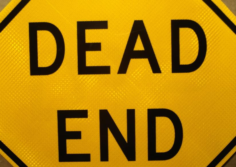 Up-close picture of our Dead End road sign showing the black lettering on a yellow background
