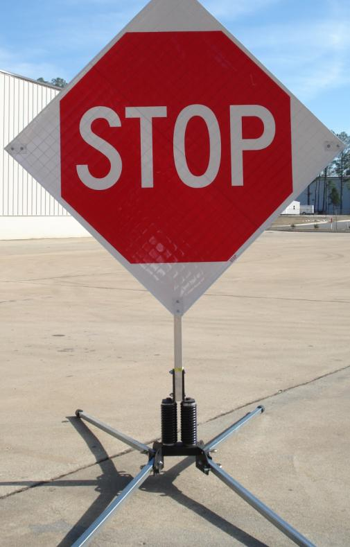The roll-up stop sign is shown with a portable RU5000 wind resistant sign stand (sold separately).