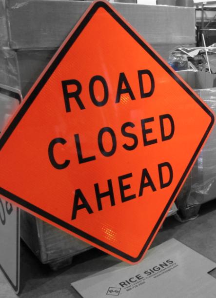 Fluorescent orange Road Closed Ahead sign shown
