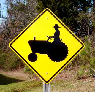 A picture of our tractor road sign. The tractor road sign shows the symbol of a tractor and is mounted on an optional u-channel highway post.